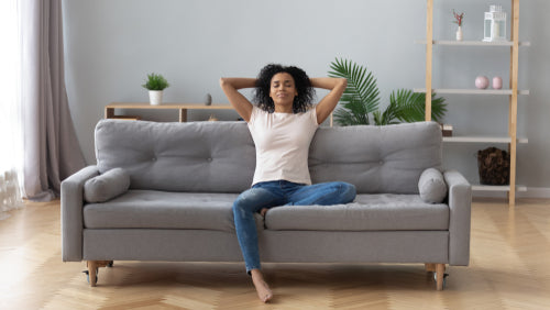 woman on couch with arms resting above head