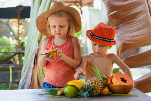 two kids playing with exotic fruit