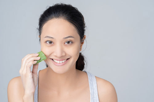 image of woman applying aloe to face