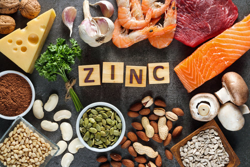 zinc spelled out in letter tiles surrounded by various healthy foods