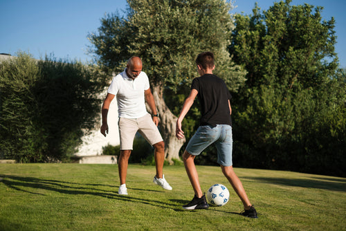 man and child playing soccer