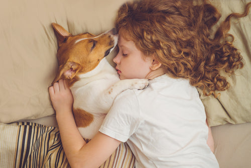 child sleeping with dog