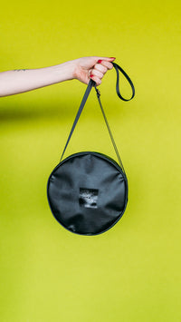 a black circular handbag is held by a female hand with red fingernails in front of a chartreuse background