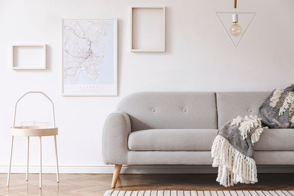 Grey sofa and white wall with neutral art on room. Hygge