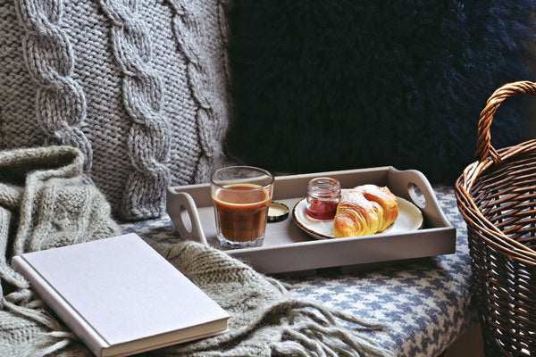 Seat with blanket, book, hot drink, pastry and honey