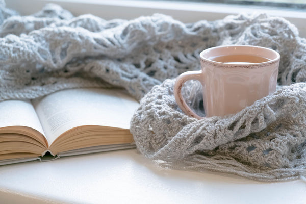 Grey blanket, book and mug of hot drink