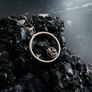 circular pendant with black meteorite