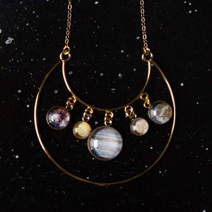gold planetary necklace on black starry backdrop