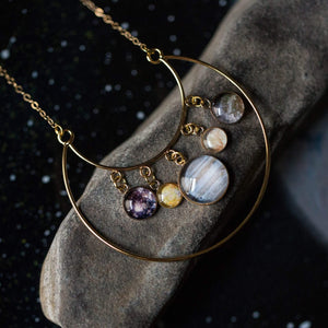 gold circular necklace with planet charms