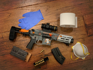 Limited Edition COVID-19 2020 Maxim Defense PDX Pistol displayed on wooden floor with ammo, mask, latex gloves, toilet paper, and scope