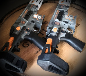 Side by side display of two Limited Edition COVID-19 2020 Maxim Defense PDX Pistols displayed on a wooden barrel