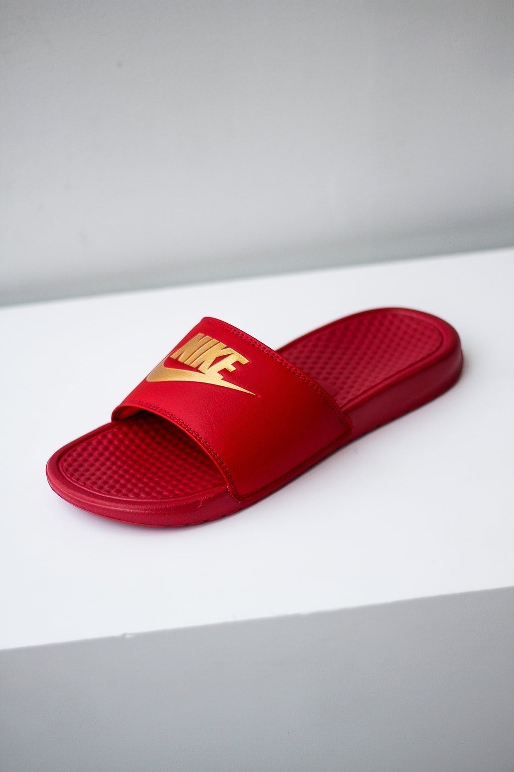 red and gold nike flip flops
