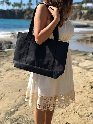 woman wearing black tote on the beach