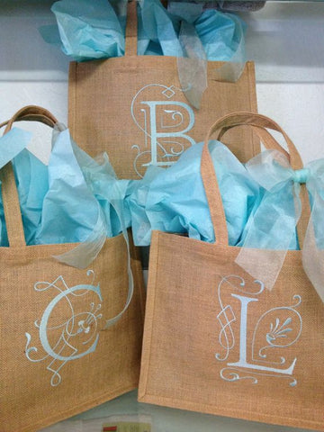 assortment of burlap tote bags with a single letter monogram