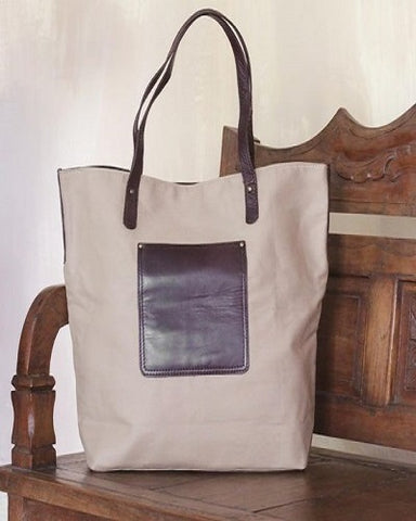 brown canvas bag with leather pocket and straps