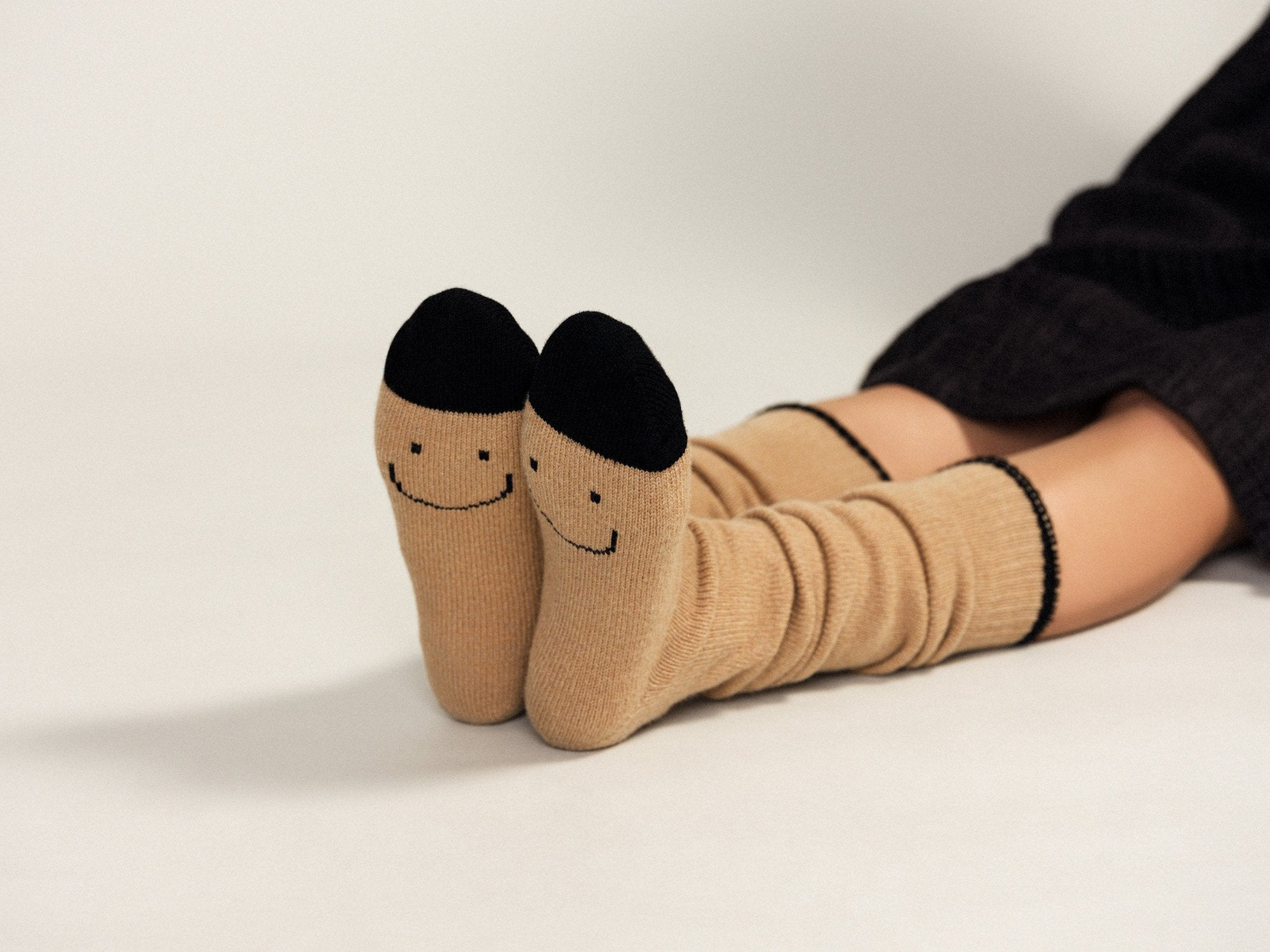Surprise wool knee high sock, tan with black detail, smiley face bottom.