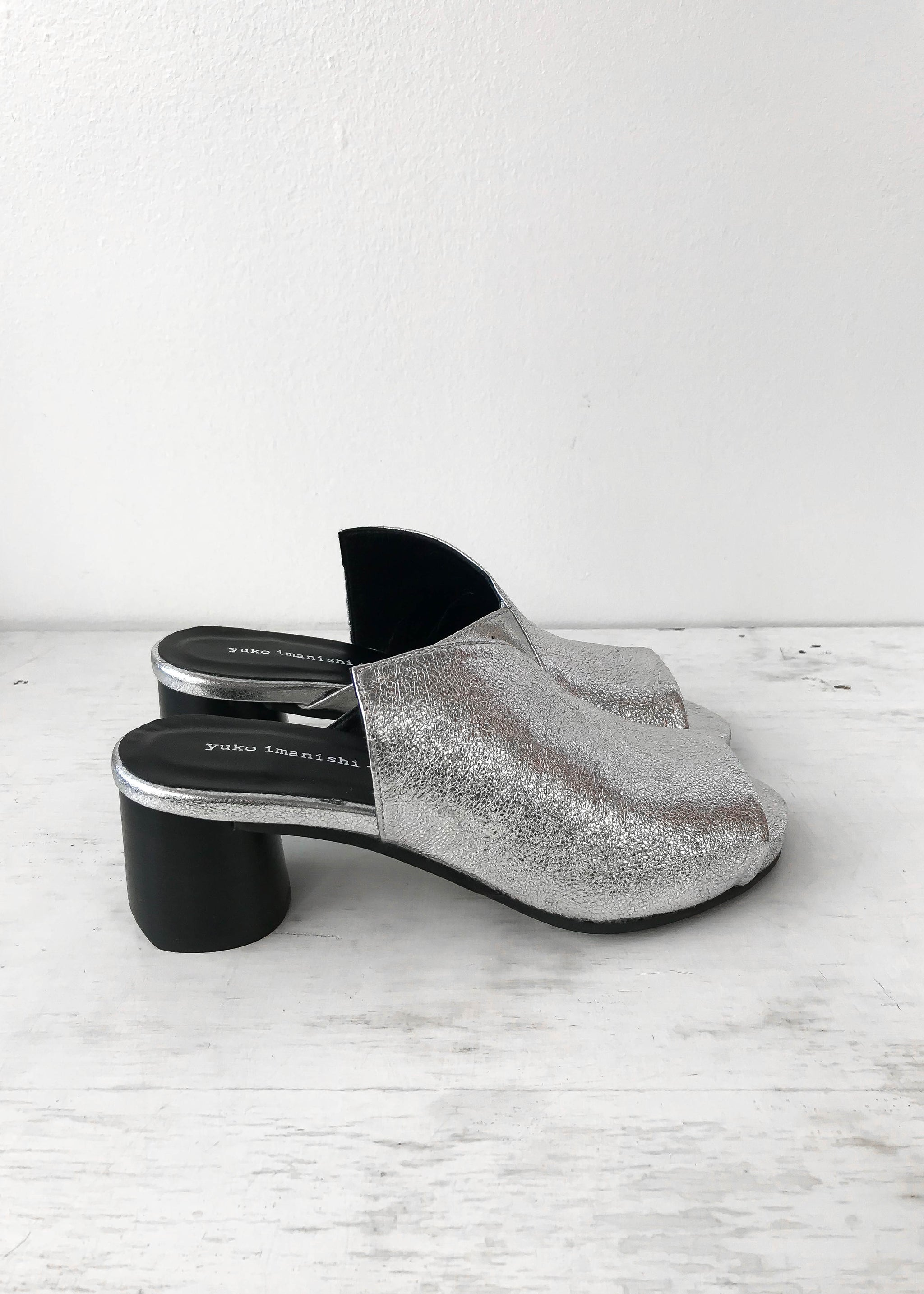 Side view of silver asymmetrical heeled mule