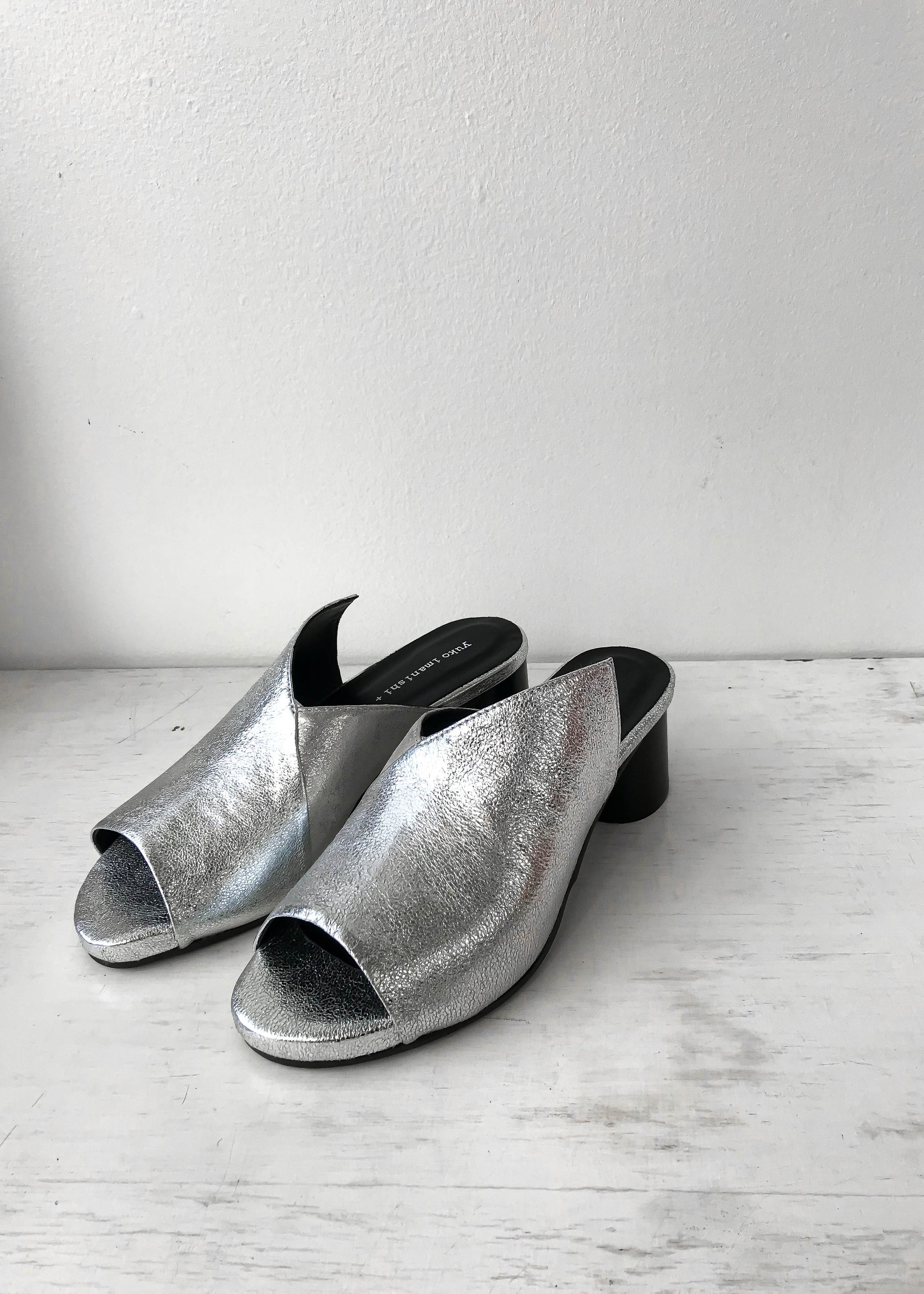 Front view of silver asymmetrical heeled mule