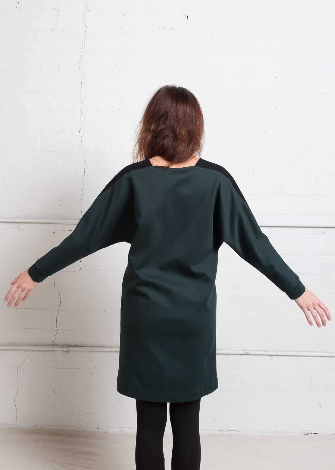 Back of deep green cotton sweater dress with pockets.