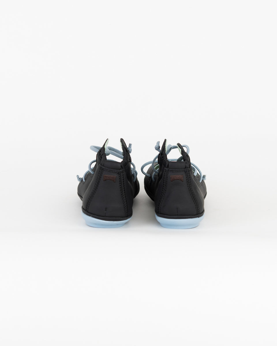 Back of black rubber flats with baby blue straps.