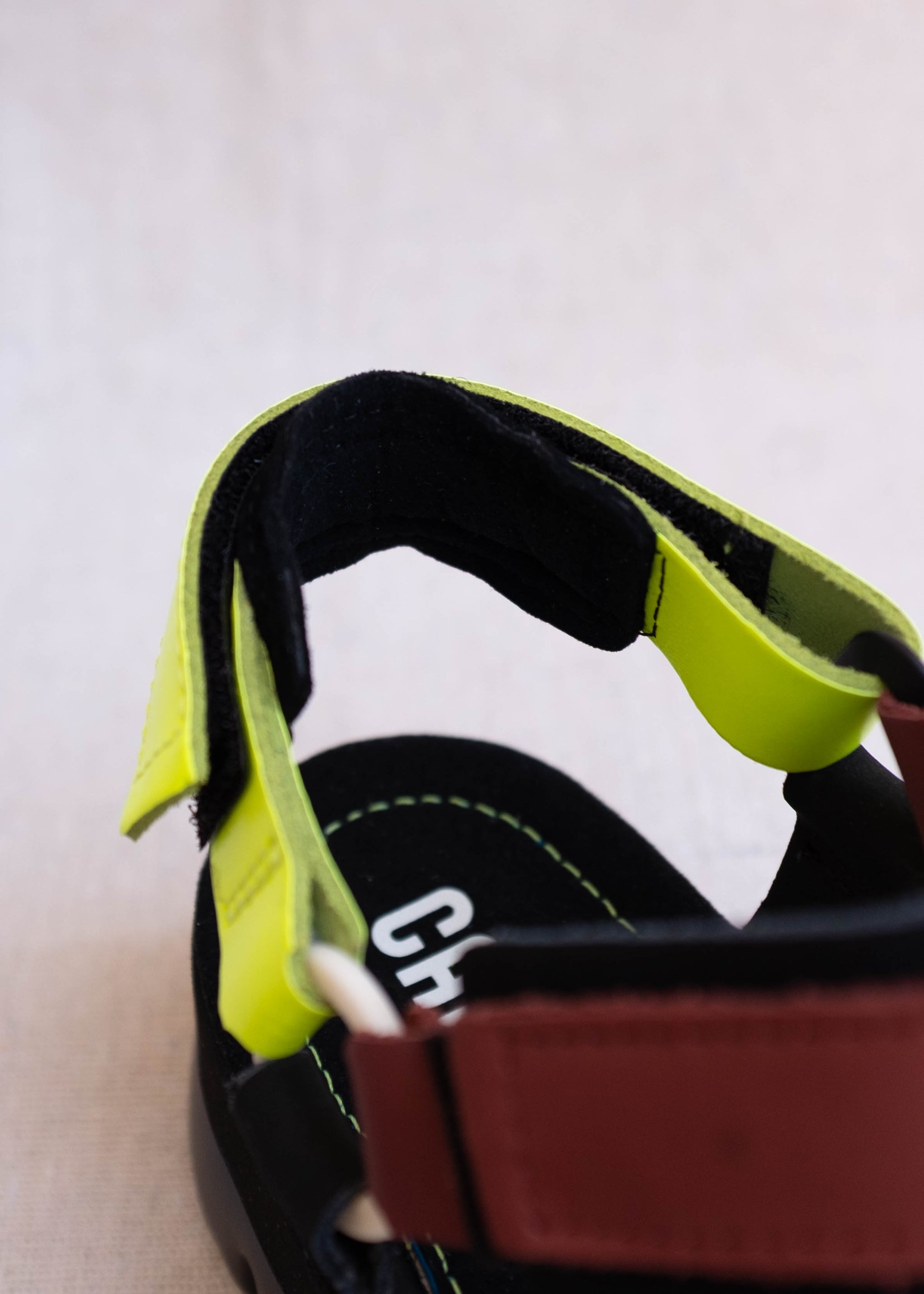 Detail view of black platform sandals with neon yellow, maroon, and black straps.