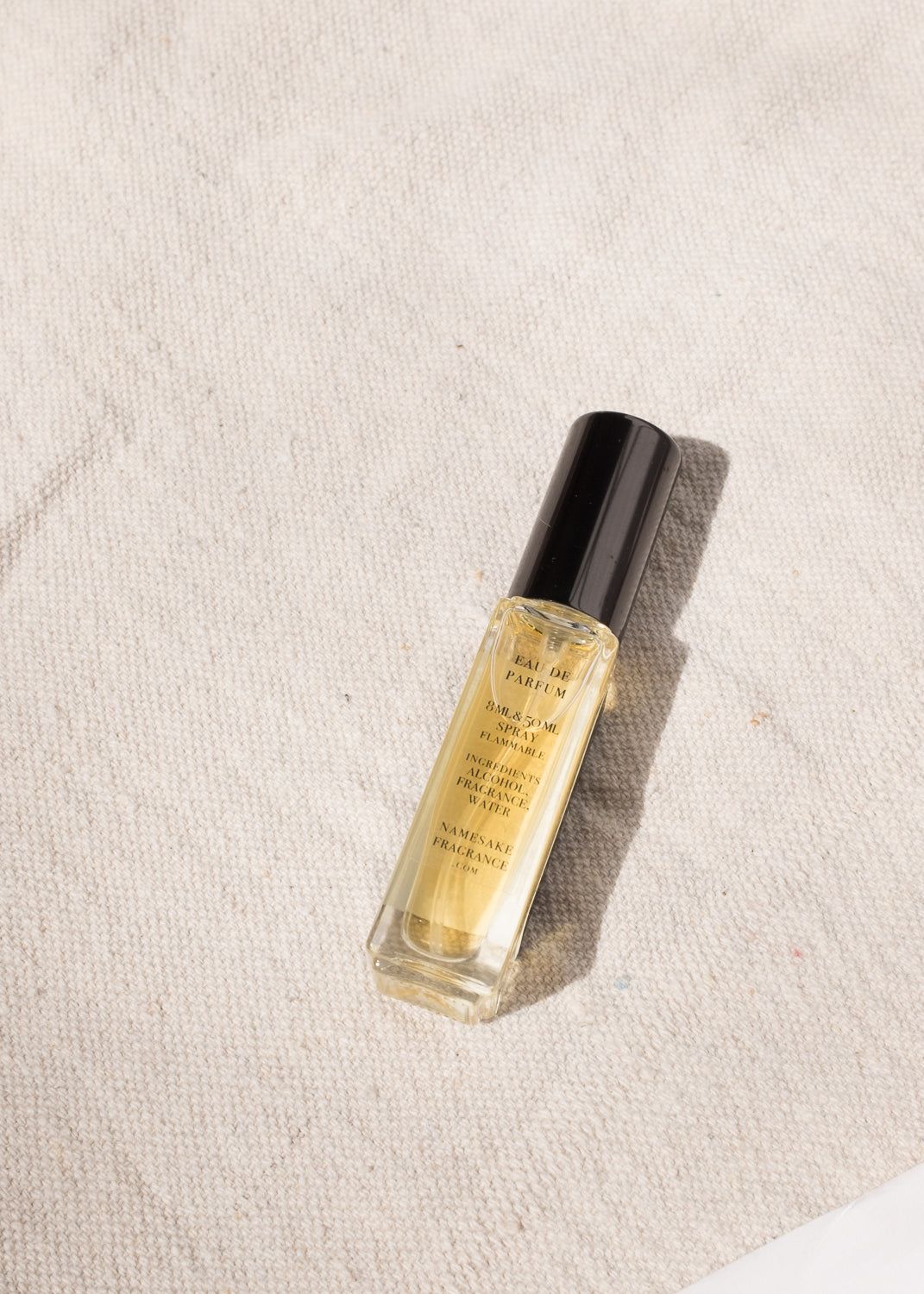 Overhead view of single rectangular perfume bottle; backside with text listing ingredients, amount, and brand.