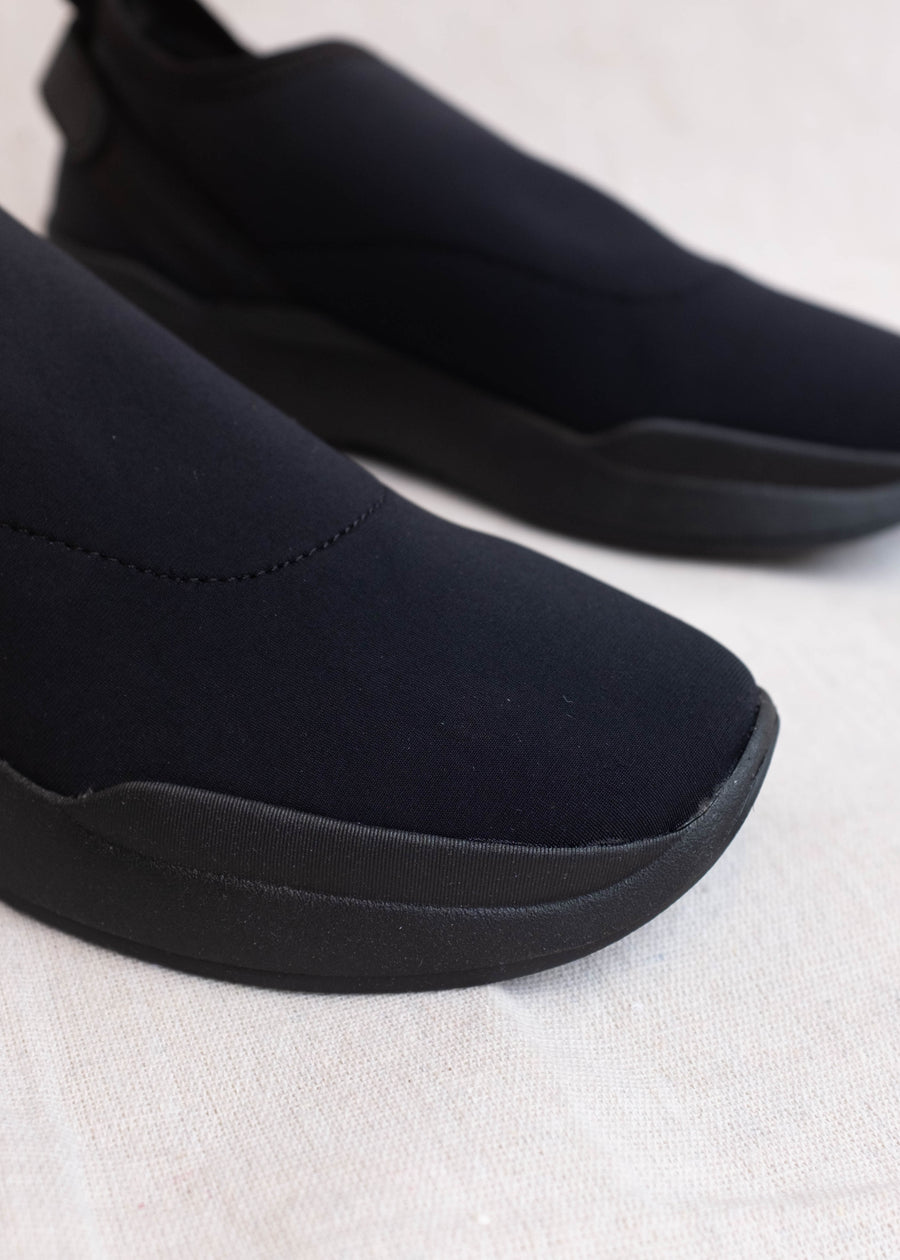 Side view of stretchy black, laceless sneakers.