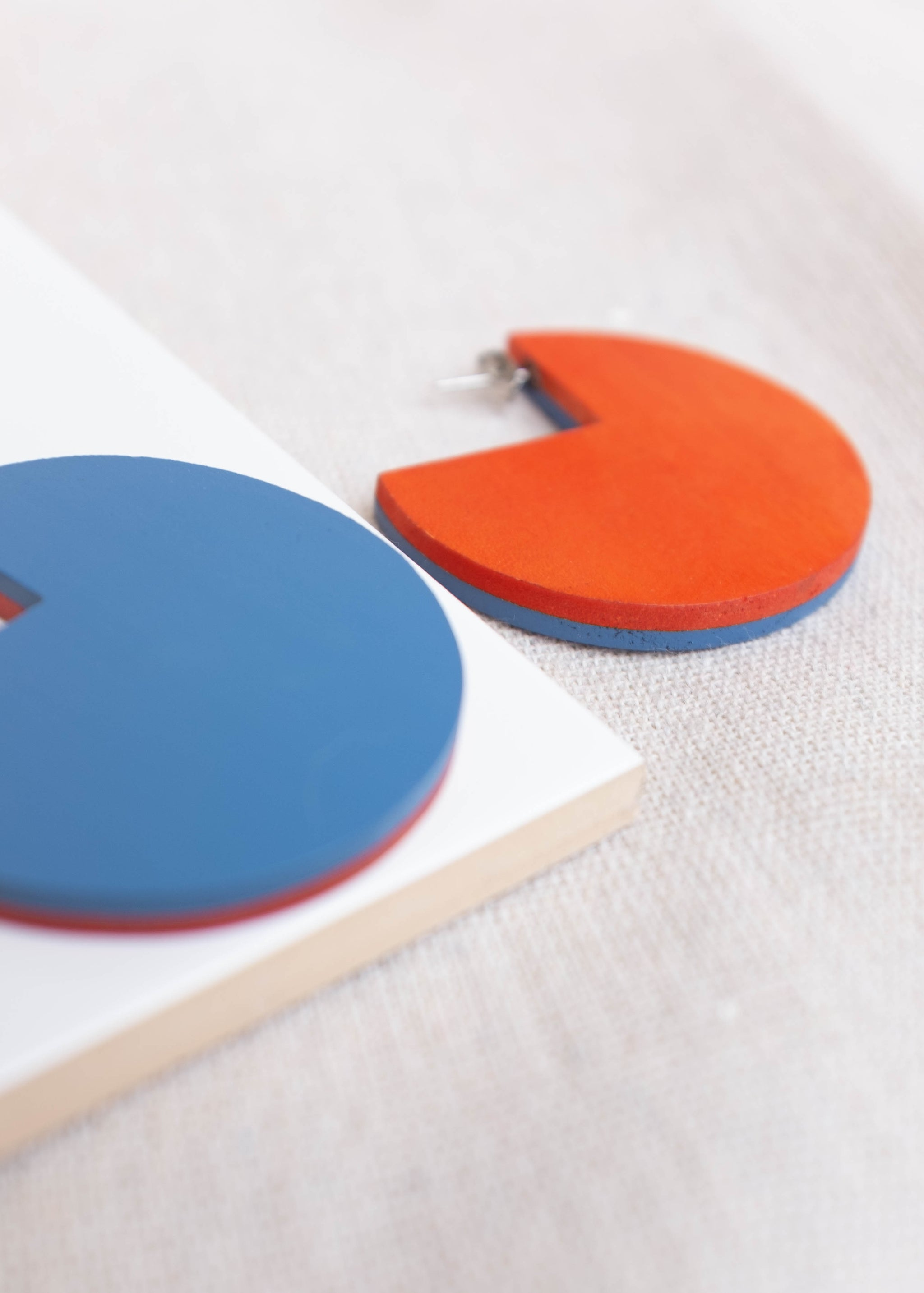 Detail view of circular, flat earrings in orange and blue.