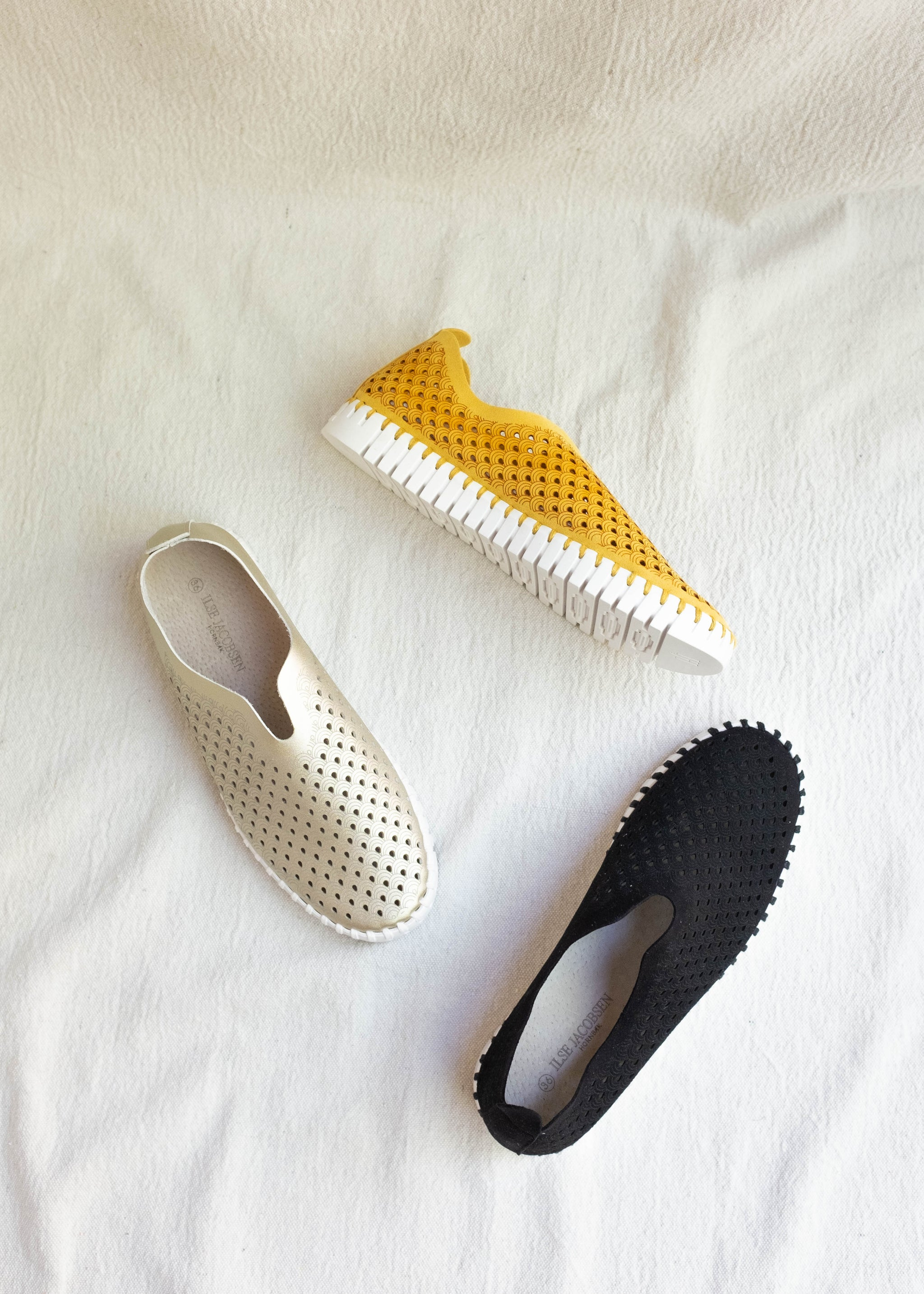 Overhead view of 3 pairs of microfiber sneakers