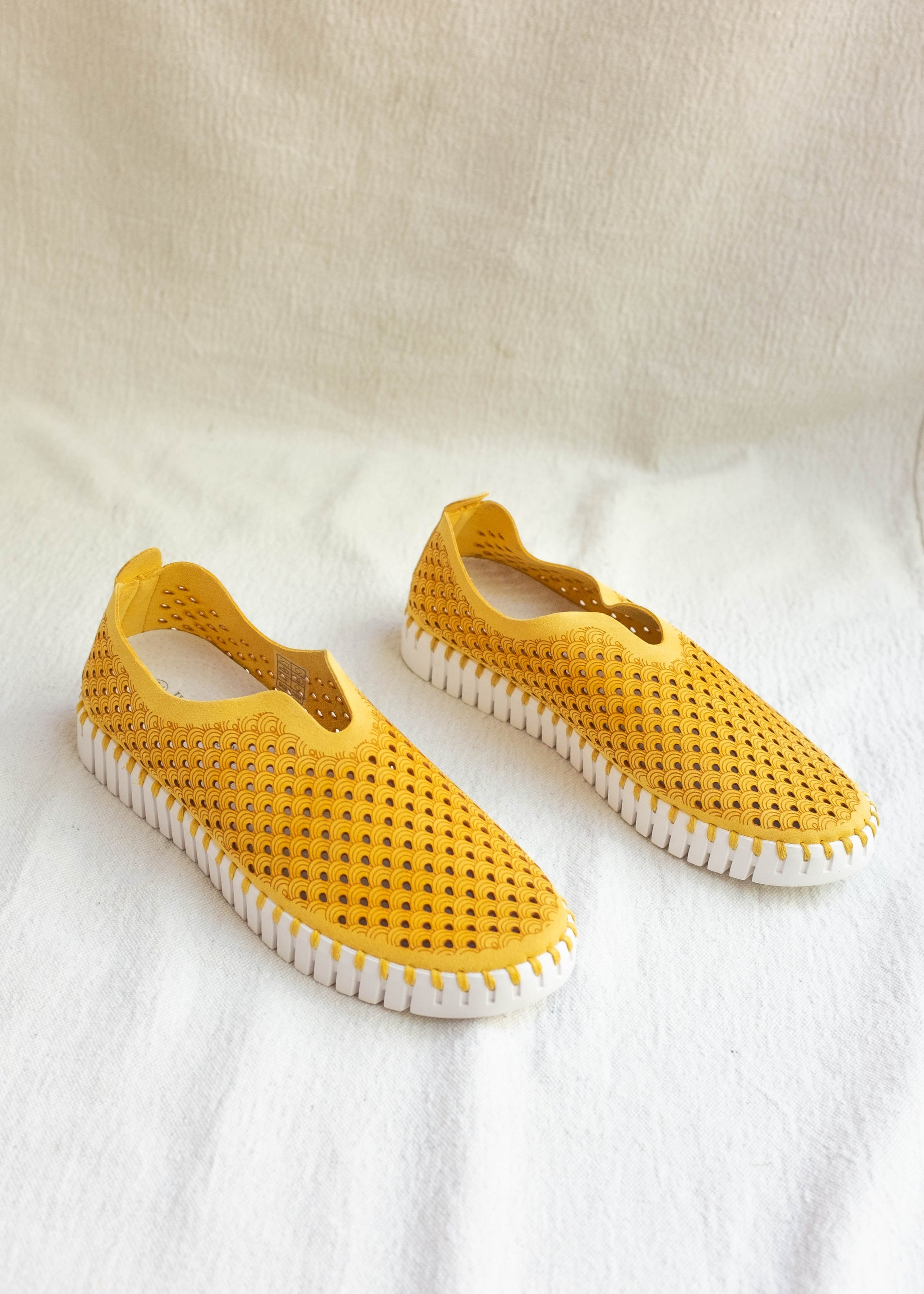 Front view of mustard yellow microfiber cutout slip-on sneakers, white soles