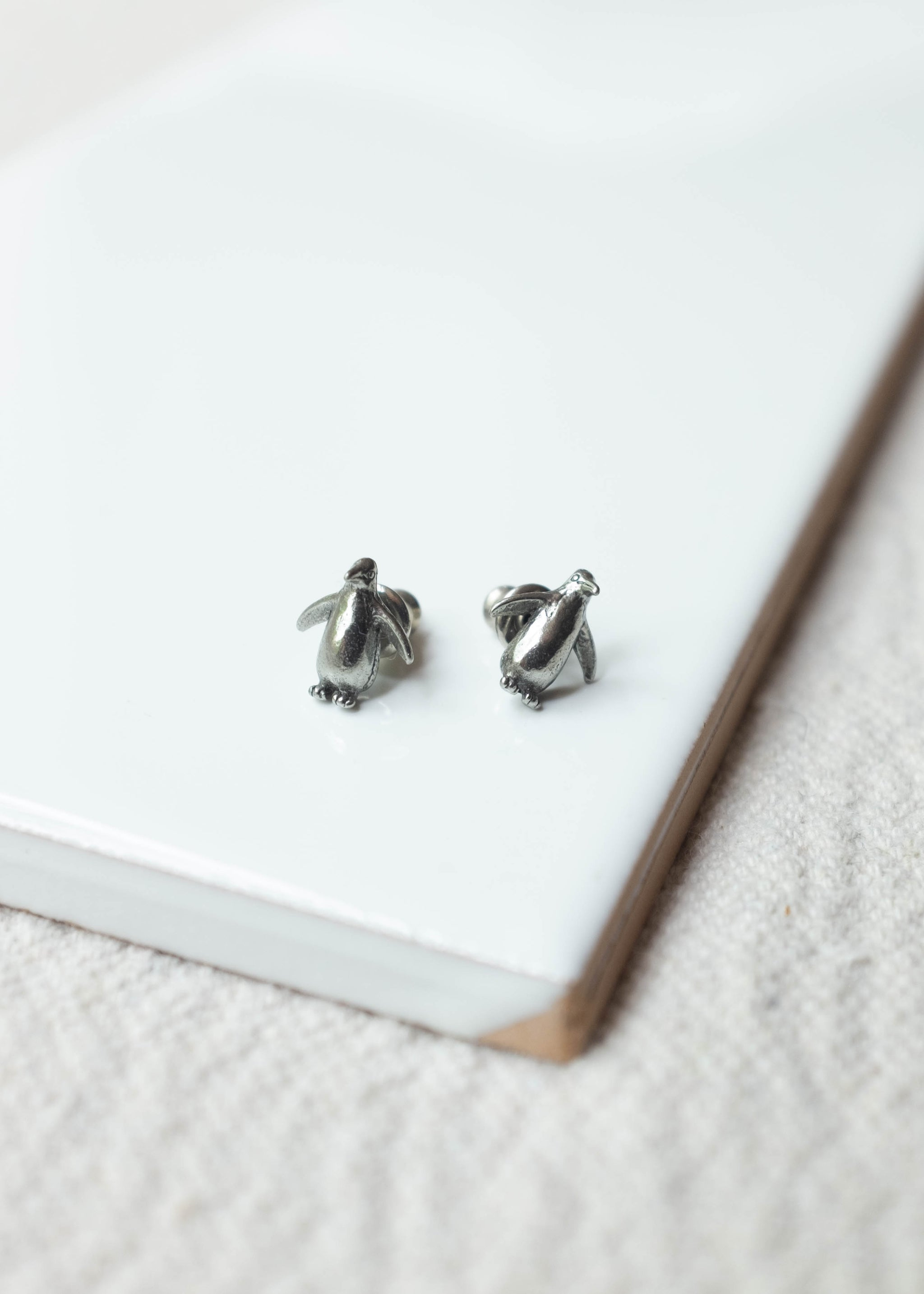 Front view of pewter penguin shaped earrings.