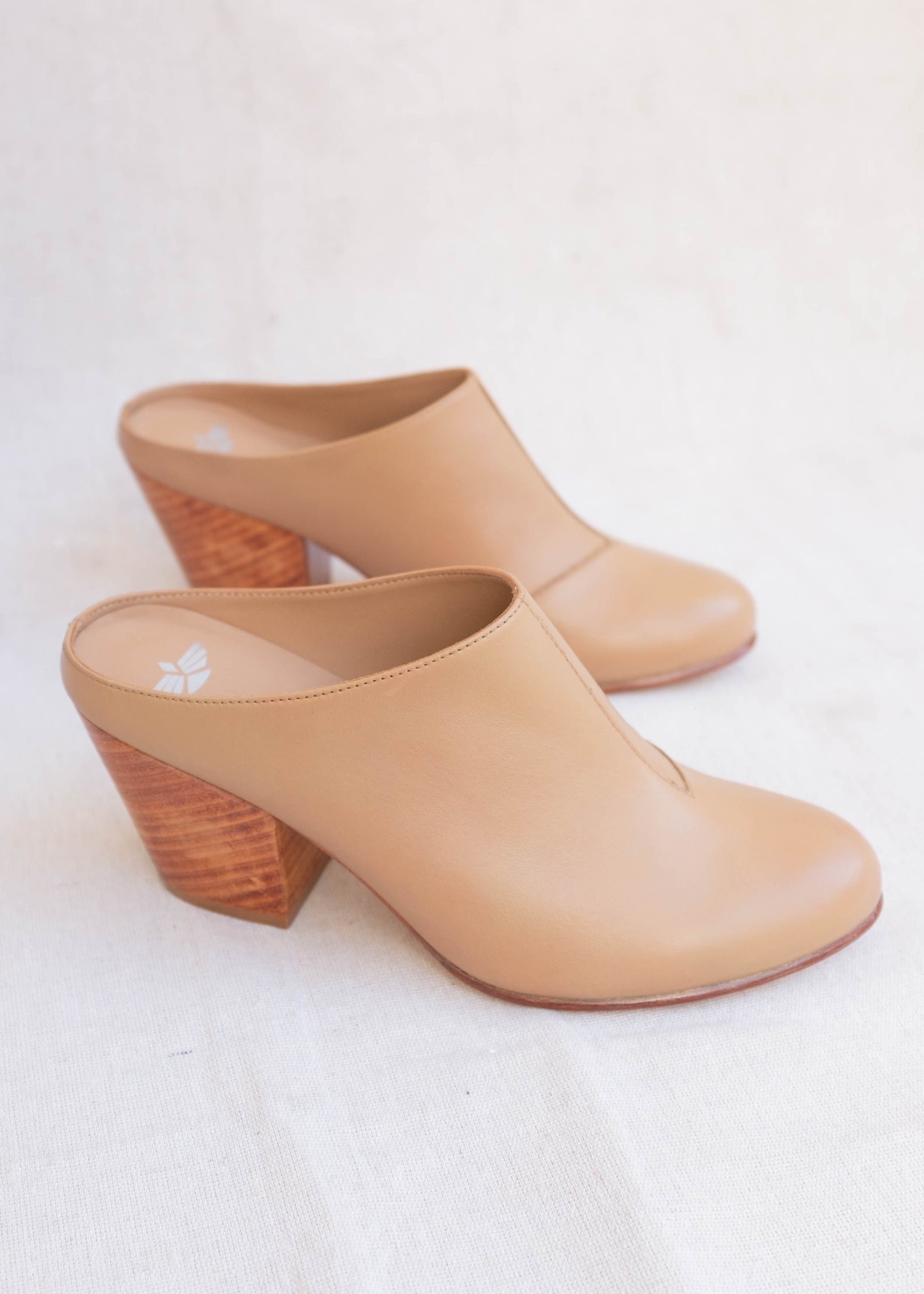 Side view of light brown leather mule with large wooden heel.