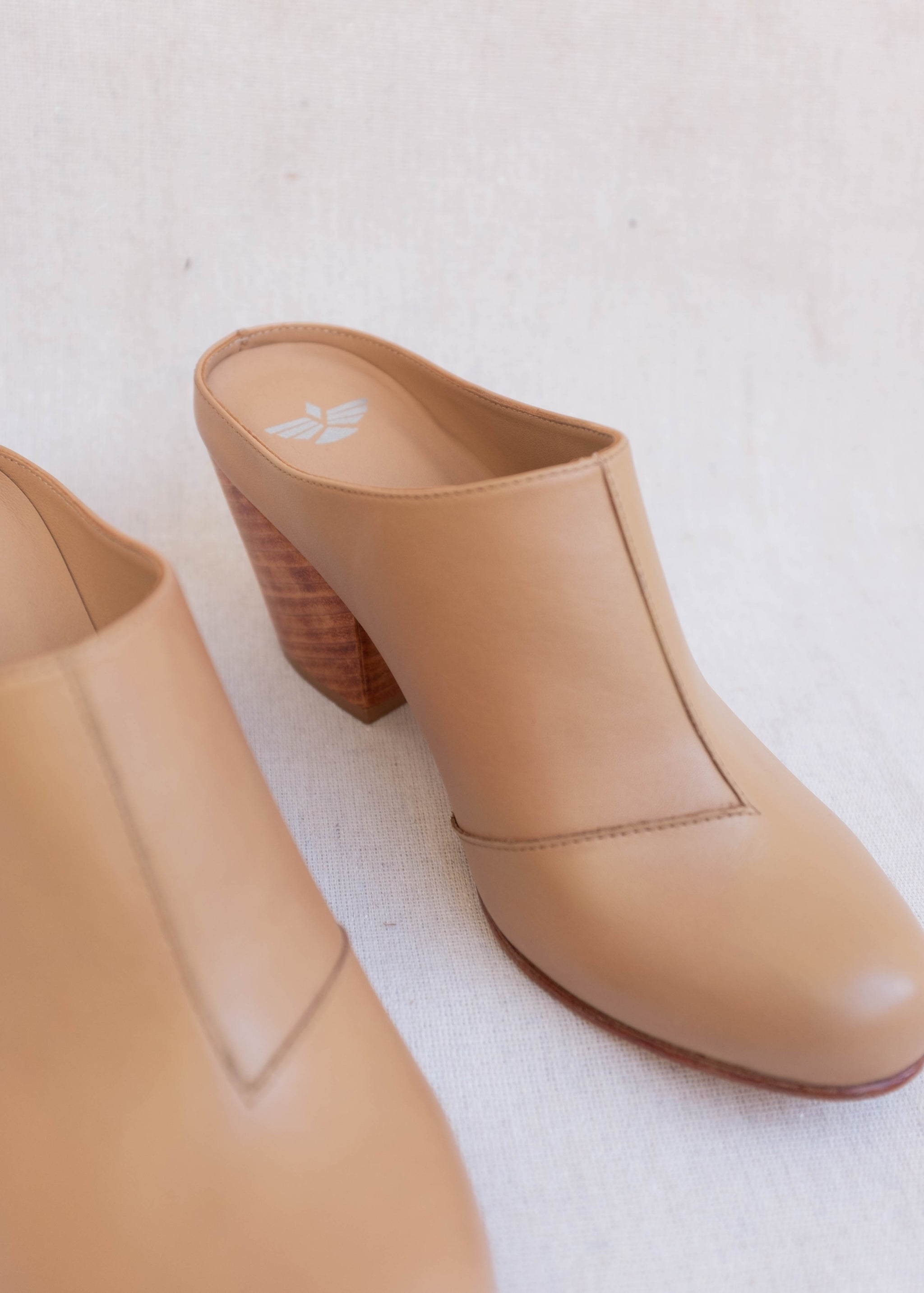 Detail view of light brown leather mule with large wooden heel.