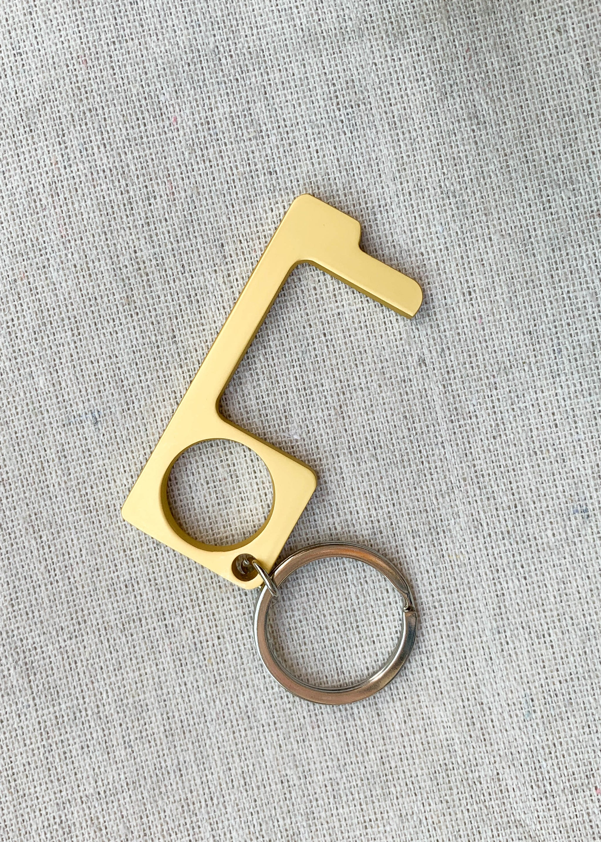 Overhead view of no-touch keychain in gold.