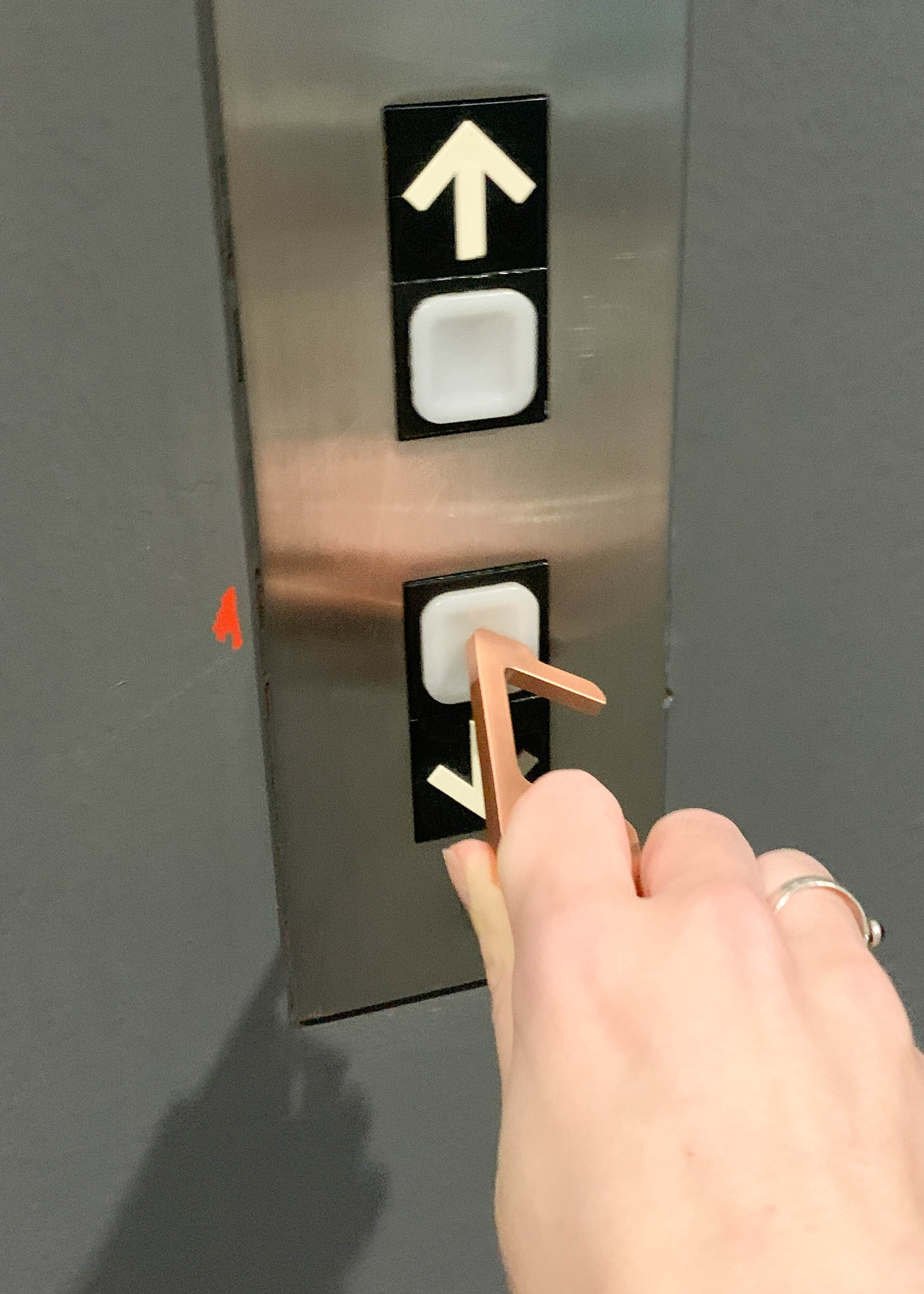 Hand using no-touch keychain on elevator button.