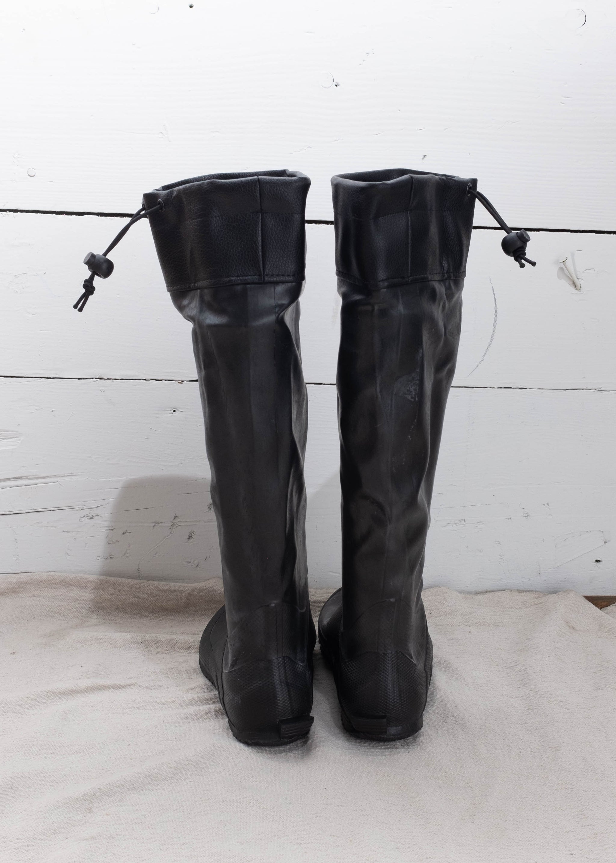Back of black heavy duty rain boots with drawstring.