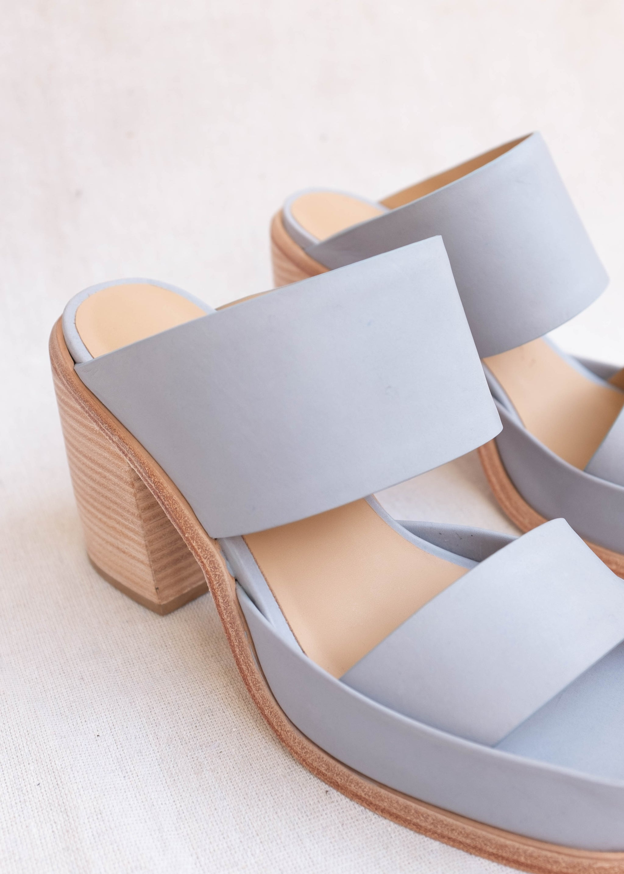 Detail view of blue-grey high-heeled sandals.