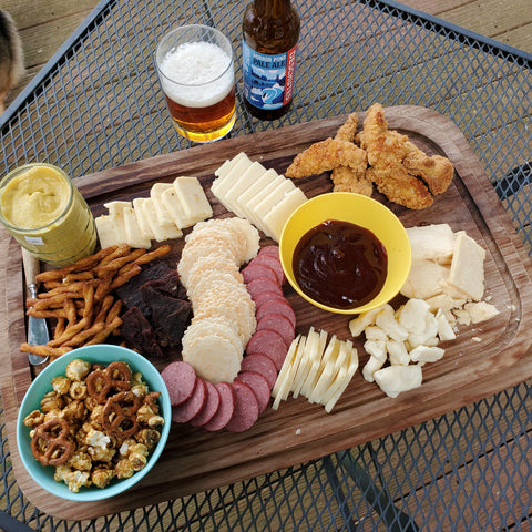 cheese board with Black Butte Porter Cheddar, sausage, pretzels, mustard and caramel corn