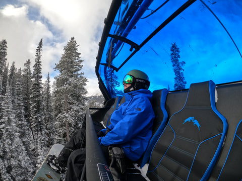 Male on a ski lift on the snowy mountains wearing a blue North Face jacket