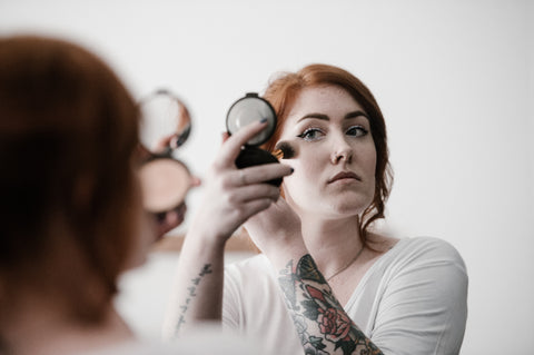 pale woman putting on makeup
