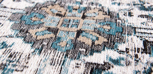 closeup of blue detail on pale faded carpet with blue detail
