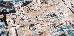 closeup of beige detail on pale faded rug