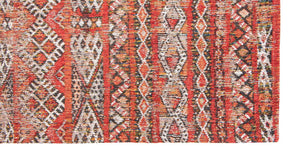 Corner closeup of rug with Morrocan nomad pattern in red tones.