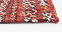 Load image into Gallery viewer, Closeup of edge of rug with Morrocan nomad pattern in red tones.