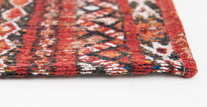 Closeup of edge of rug with Morrocan nomad pattern in red tones.