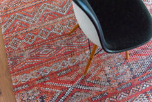 Load image into Gallery viewer, Rug with Morrocan nomad pattern in red tones on wooden floor.