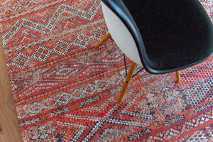 Rug with Morrocan nomad pattern in red tones on wooden floor.