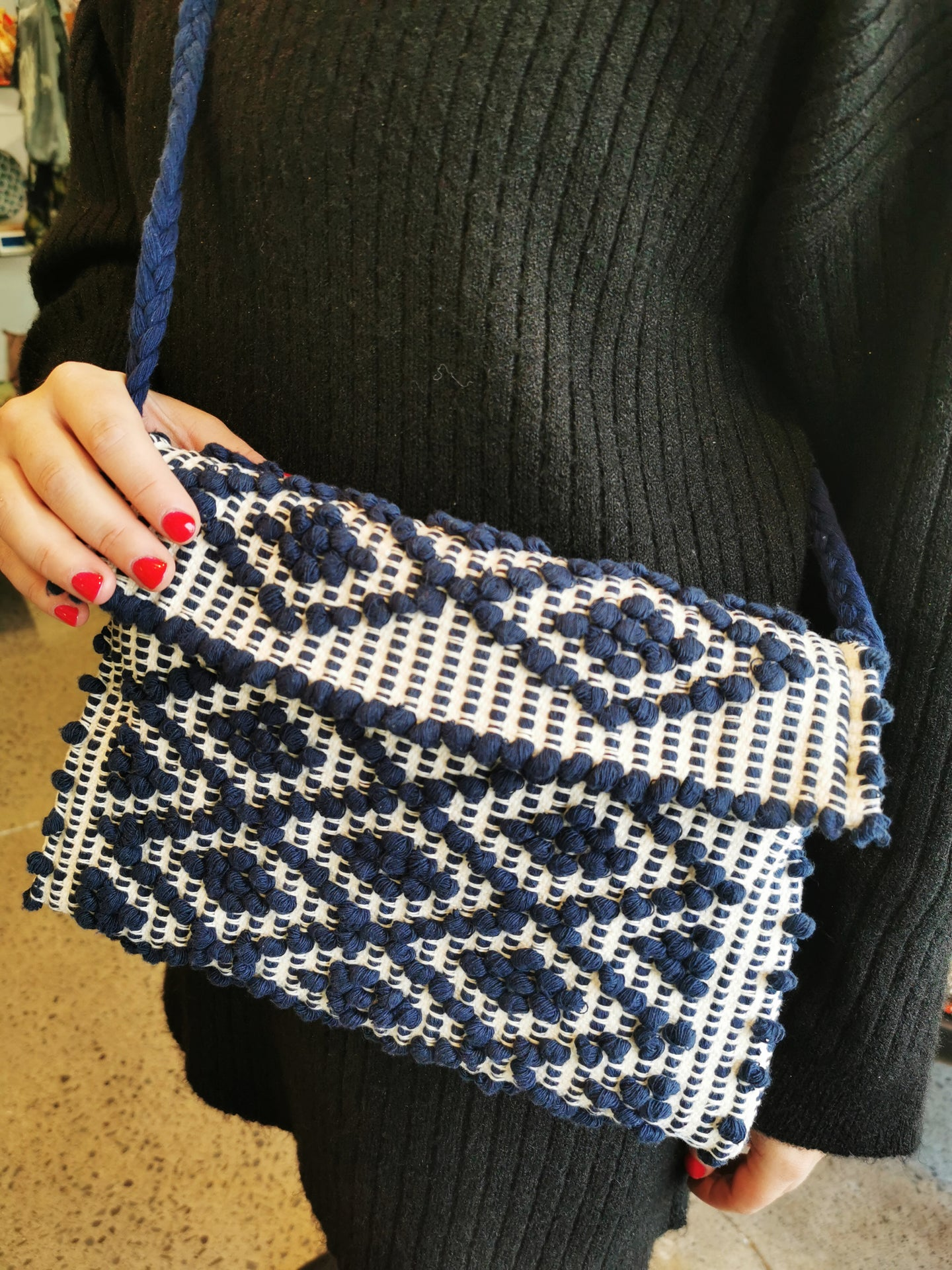Crossbody eco friendly clutch bag with white and blue woven detail on moel