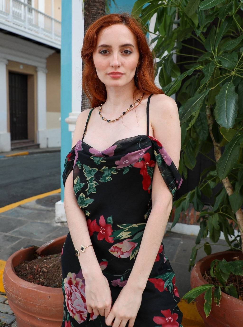 Model wearing Vaed By Va's Aubrey dress with blue house in the background in old san juan