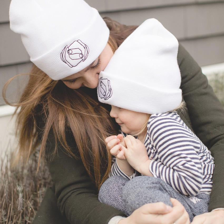 A woman and her daughter wearing the white fleece lined MHIY™ Beanie for sale exclusively by My Hand In Yours - a website created to sell objects of comfort as gifts that support Children's Hospital Los Angeles